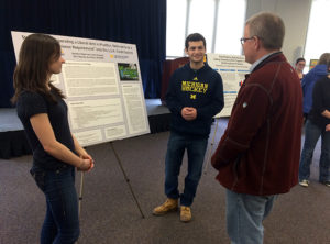 Students Lauren Shepard and Brandon Hopen discuss their project with Tim McKay, Arthur F. Thurnau Professor of Physics.