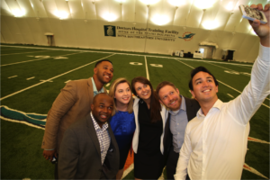 University of Michigan Ross MBA students take a selfie on the 50-yard line at the Miami Dolphins training facility in Davie, Fla.