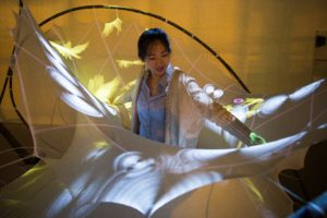 Architecture student Karen Duan interacts with a 3-D structure titled StretchPLAY, one of the pieces designed to encourage responses from autistic children. Pressing on the elastic textile in particular spots activates animations that are projected across various areas of the textile surface. (Photo by Sean Ahlquist)