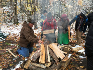 Students and faculty help build the fire that will heat rocks for the sweat lodge.