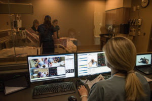 Clinical instructor Maureen Westfall at her control bank behind a one-way mirror in the Clinical Learning Center at the U-M School of Nursing. She operates Victoria wirelessly and students respond to the various medical conditions she presents. Credit: Michigan Photography