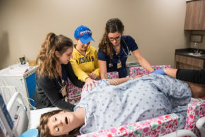 U-M Nursing students turn the Victoria mannequin on her side during a programmed seizure. Credit: Michigan Photography