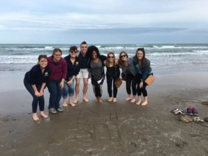 "After writing ""SPH"" and a block ""M"" in the sand, School of Public Health spring break students take a photo at South Padre Island upon their arrival for a community health assessment project in Hidalgo County, Texas. They are, from left, Liz Timoszyk, Elana Elkin, Peggy Korpela, Christopher Bush, Megan Edmonds, Chelsea Abshire, Grace Christensen and Julia Porth. Photo Courtesy of the School of Public Health"